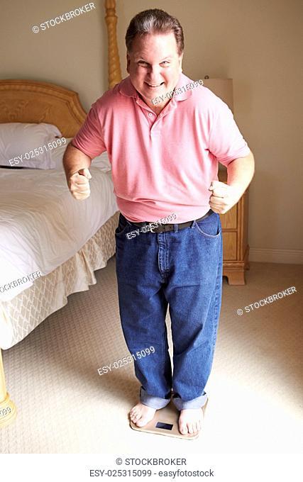 Happy Overweight Man Standing On Scales In Bedroom