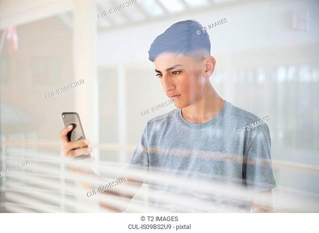 Teenage boy reading text message on cellphone by glass wall