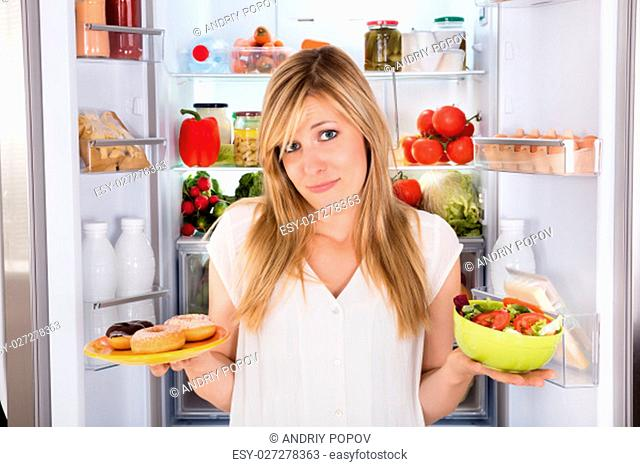 Confused Young Woman Holding Salad And Plate Of Donut Near Refrigerator