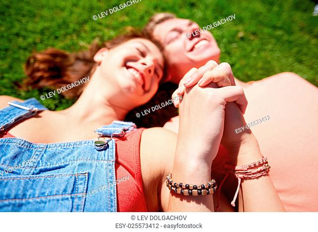 love and people concept - close up of happy teenage couple lying on grass and holding hands with wristbands at summer