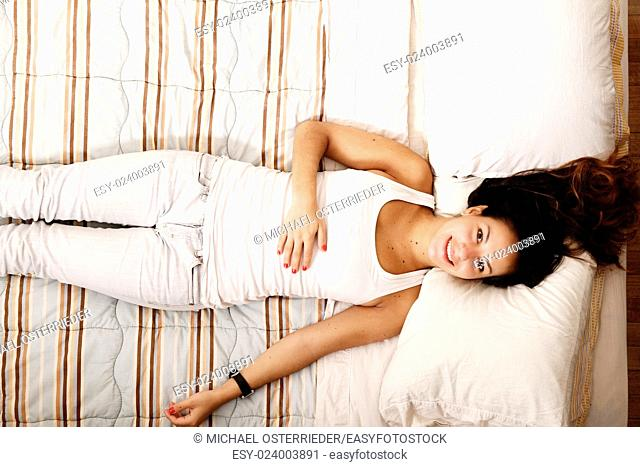 A young woman laying on the bed