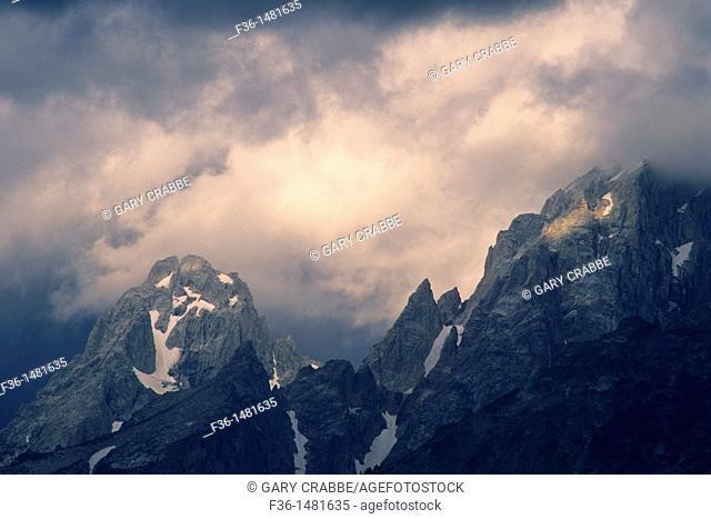 Sunlight on storm clouds near the summit of the Grand Tetons, Grand Teton Nat'l  Pk , WYOMING