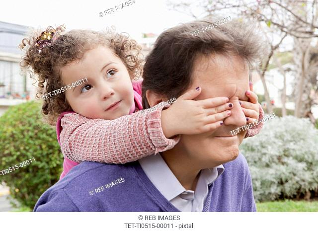 Girl covering father's eyes during piggyback ride