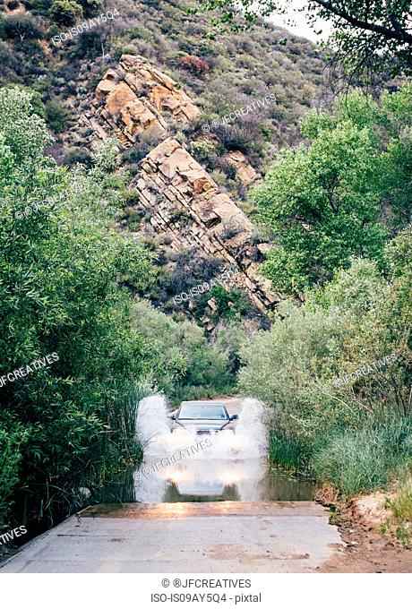 Off road vehicle driving through deep water on rural road, Santa Barbara, California, USA
