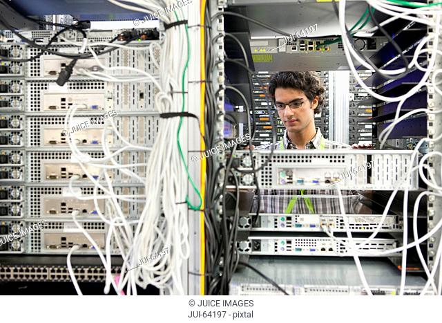 Technician working on server in server cabinet