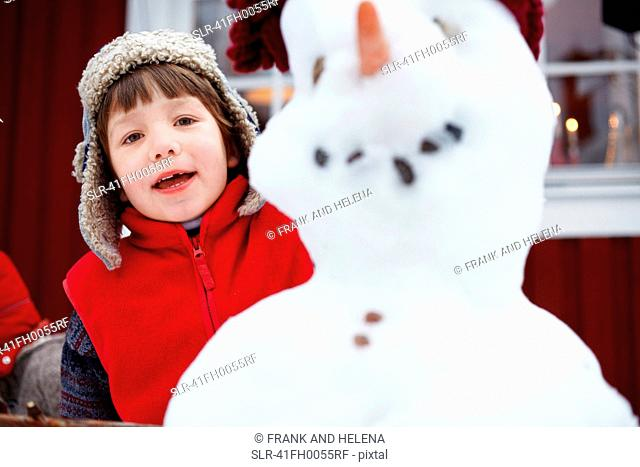 Boy standing behind snowman