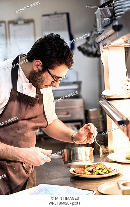 Bearded chef wearing glasses and apron standing in commercial kitchen at counter, plating food