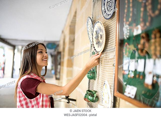 Spain, Baeza, smiling young woman watching wall plates in front of gift shop