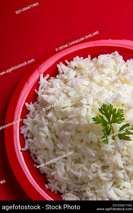 Cooked plain white basmati rice in a red plate on red background