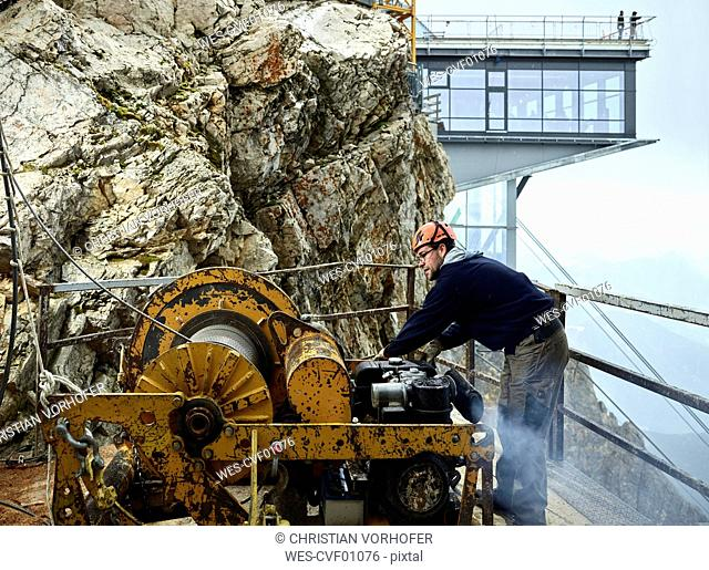 Germany, Bavaria, Garmisch-Partenkirchen, Zugspitze, installer working with rope pulley on goods cable lift