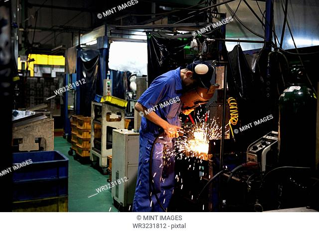 Man wearing blue overall and welding mask standing in factory, welding metal, sparks flying