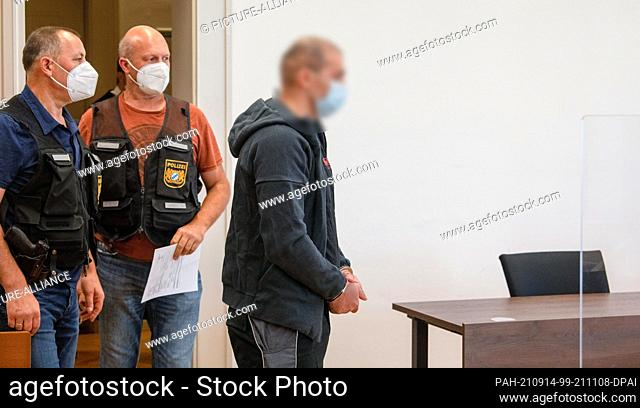 14 September 2021, Bavaria, Memmingen: In the district court, two police officers lead a man into the jury room. He is charged with attempted murder