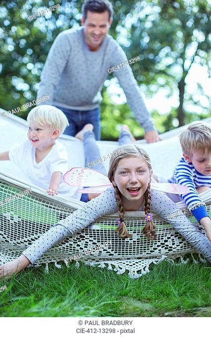 Father pushing children in hammock outdoors