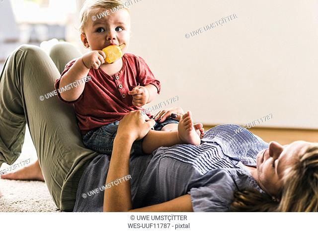 Mother and son at home eating ice lolly