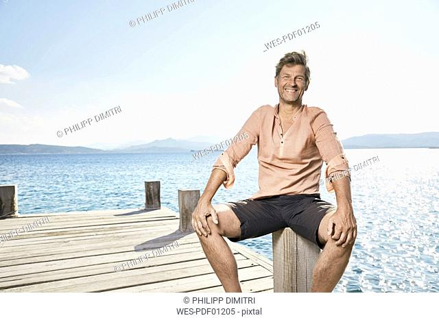 Portrait of smiling man sitting on jetty