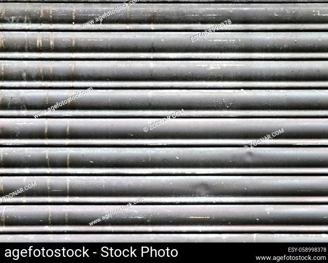 dirty old grey stained horizontal closed steel rolling security shutters