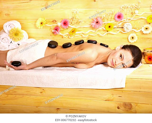 Woman getting stone therapy massage in wooden spa