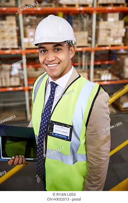 Portrait smiling manager with digital tablet in distribution warehouse