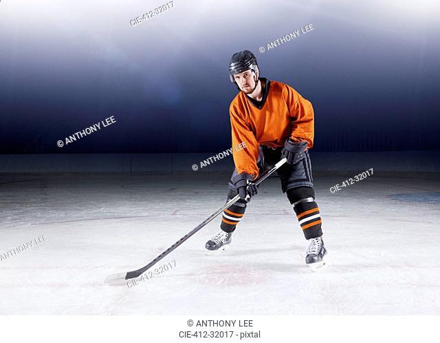Portrait confident hockey player in orange uniform on ice