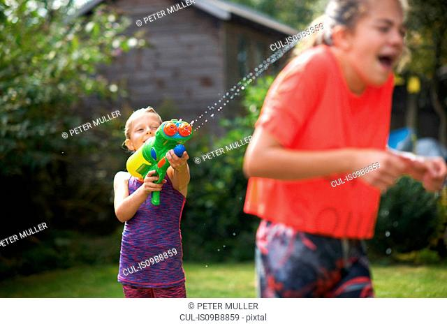 Boy squirting his teenage sisters with water gun in garden