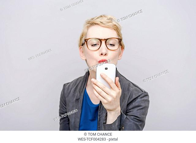 Blond woman pouting mouth taking a selfie with her smartphone