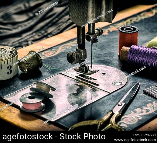 Closeup of an old sewing machine and accessories for sewing, scissors, needles and a tailor tape on a table. The concept of sewing accessories