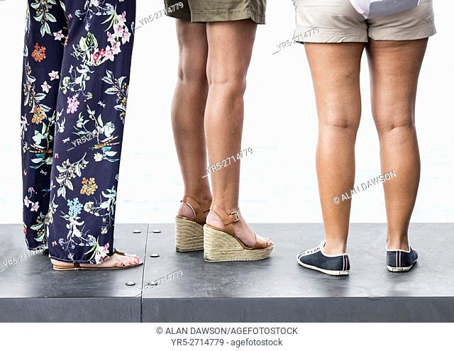 Three woman wearing different kinds of footwear: heels and flat