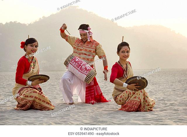 Bihu women dancing with brass plates as Bihu man plays on a dhol