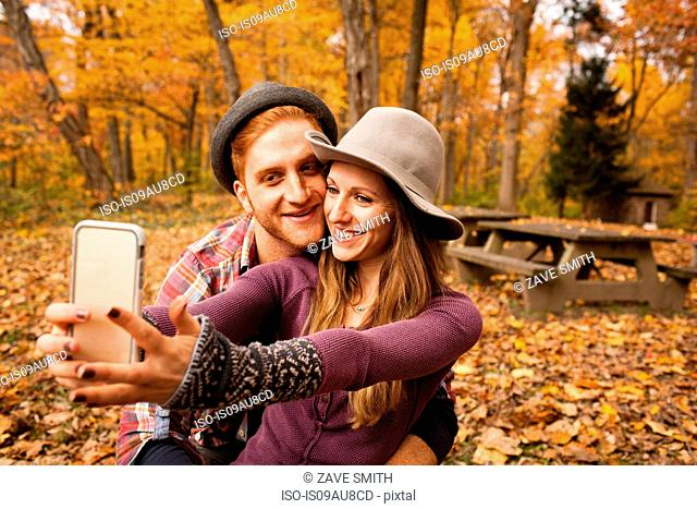 Young couple taking smartphone selfie in autumn forest