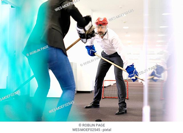 Businesswoman and businessman playing ice hockey in office