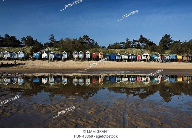 Row of beach huts reflected in the stillness of the remaining low tide in the warm early morning summer light, Wells-next-the-sea, North Norfolk Coast