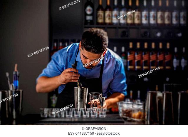 Bartender preparing an alcoholic beverage in a restaurant bar