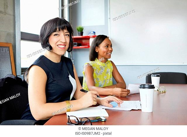 Two women sitting at meeting room table, woman in foreground looking at camera