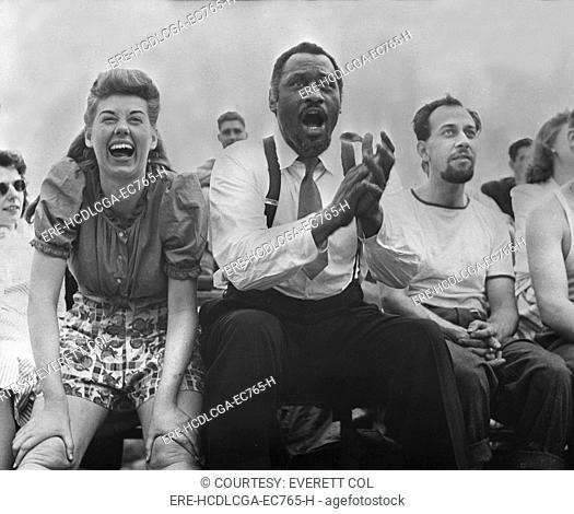 New York City, Paul Robeson center, Jose Ferrer right, watching softball with other members of Othello production, Central Park, circa 1943-1944