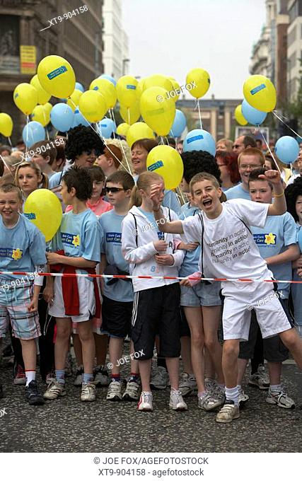 crowd of children competitors with balloons line up at the start line of the belfast marathon fun run 2008 belfast city centre northern ireland