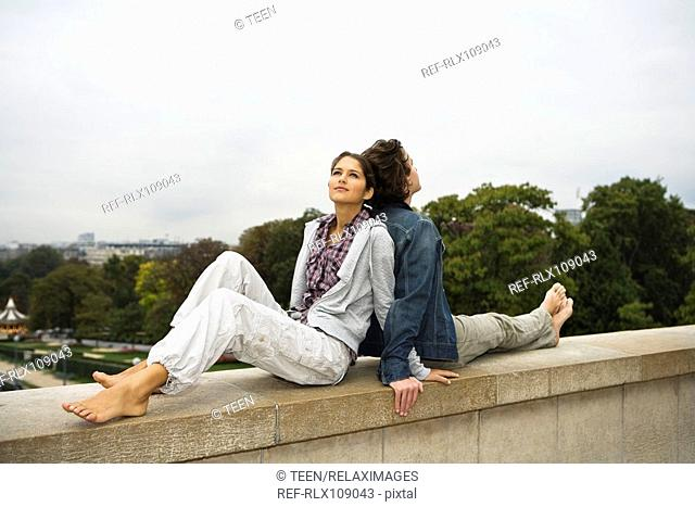 Young couple lying back to back on wall, Paris France