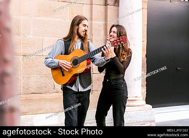 Portrait of two happy young musicians in the city