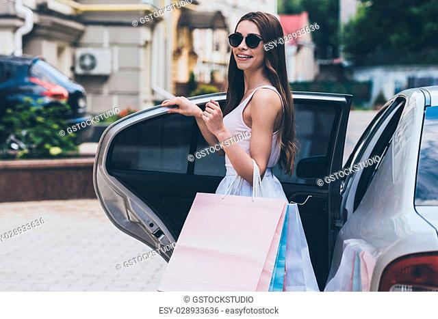 Shopping never ends. Beautiful young woman carrying shopping bags and smiling while standing near the car on the street