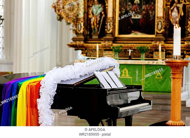 Boa and gay pride flag on grand piano in church