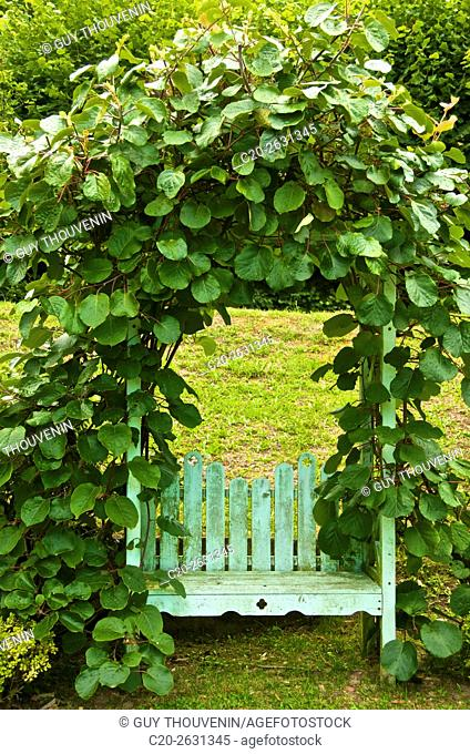 Romantic wooden bench under a green harbour in a garden, Cotentin, 50, Normandy, France