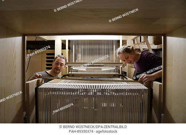 """Construction manager Ansgar Gaulke and apprentice Helena Heckenbach of the Berlin Organ Construction company """"""""Karl Schuke"""""""" works on the key tracts of a new..."""