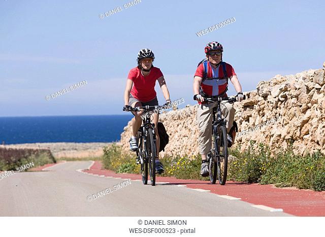 Spain, Menorca, Punta Nati, Man and woman cycling on road