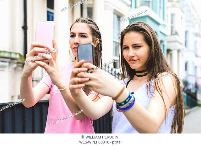 Two teenage girls in the city standing side by side taking selfies