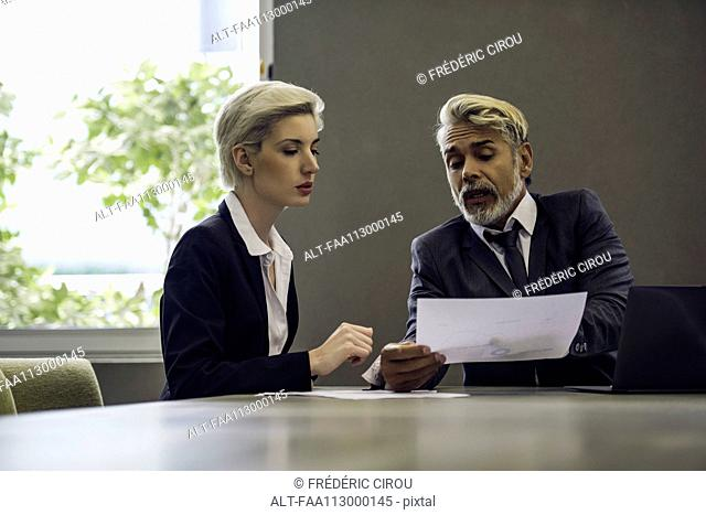Woman and man in office discussing document