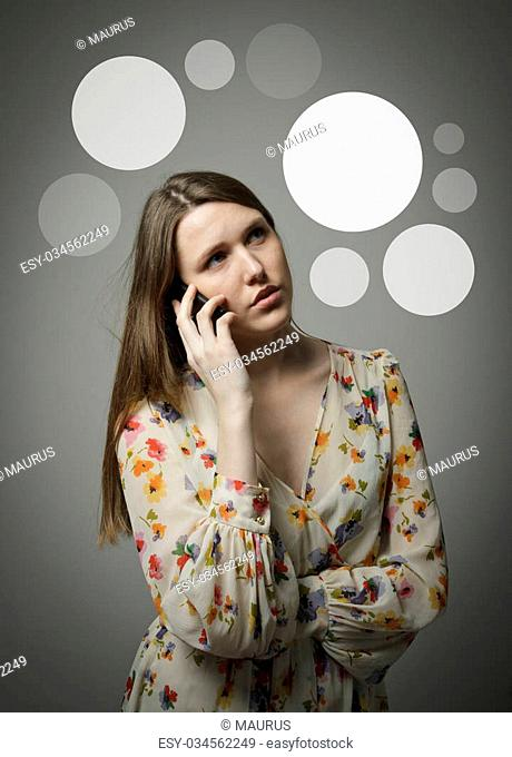 Beautiful woman talking on the phone and gray bubbles over her head
