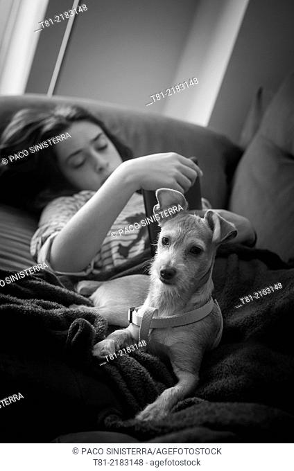 Teenage girl with her dog on the couch at home. Peniscola, Castellón, Valencia, Spain