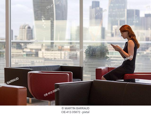 Businesswoman texting with cell phone in urban lounge with city view
