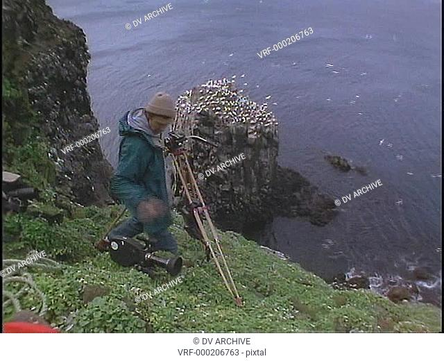 A cinematographer films birds