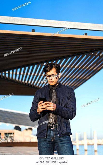 Portrait of fashionable young businessman wearing glasses and tie looking at cell phone