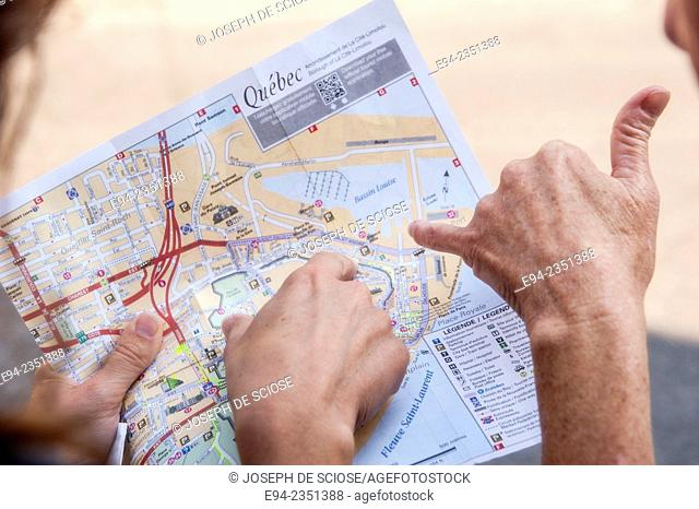 The hands of 2 women pointing at a map of Quebec City